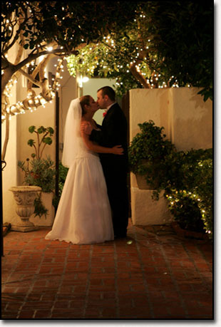 Bride and Groom Kiss in twinkly lights